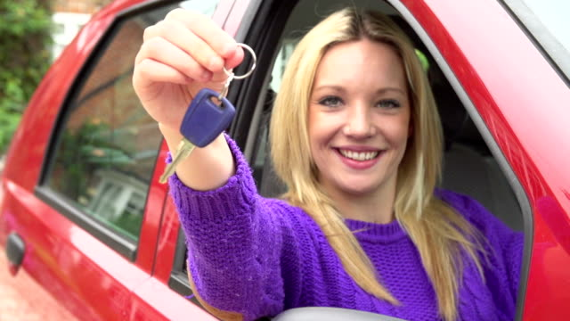 Slow Motion Shot Of Teenage Girl Sitting In Car Happy teenage girl holds out key to car and focus pulls from her face to the key in slow motion sequence.Shot on Sony FS700 in PAL format at a frame rate of 200fps car rental stock videos & royalty-free footage