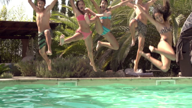 Slow Motion Shot Of Teenagers Jumping Into Swimming Pool video
