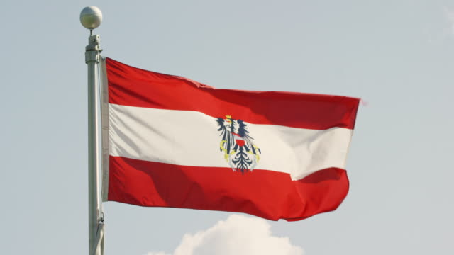 vidéos et rushes de slow motion shot of the flag of austria blowing in the wind on a sunny day - autriche
