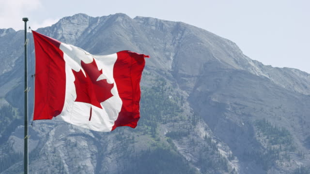 Slow Motion Shot of the Flag of Canada Blowing in the Wind with a Mountain in the Background on a Sunny Day