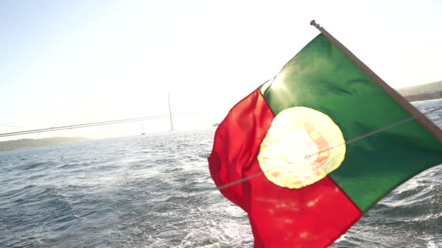 vídeos de stock e filmes b-roll de slow motion shot of the portuguese flag on the back of a boat - people lisbon