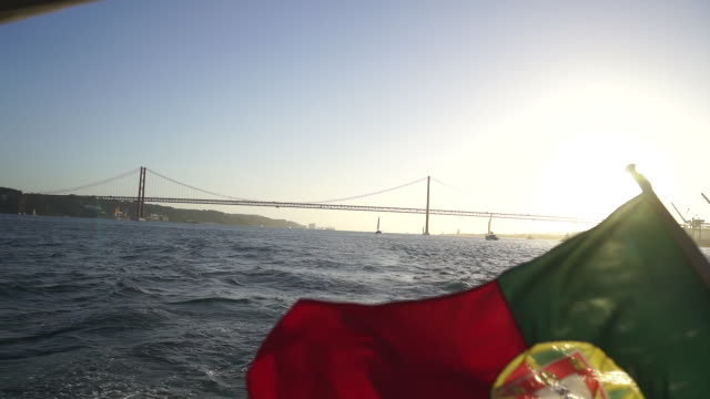 slow motion shot of the portuguese flag on the back of a boat - эскапизм стоковые видео и кадры b-roll