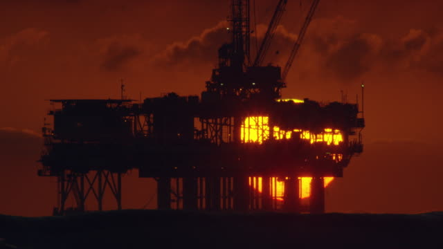 Slow Motion Shot of the Sun Setting on the Horizon as Waves Beat against the Shore off of Huntington Beach in Southern California with an Offshore Oil Drilling Rig Platform in the Distance