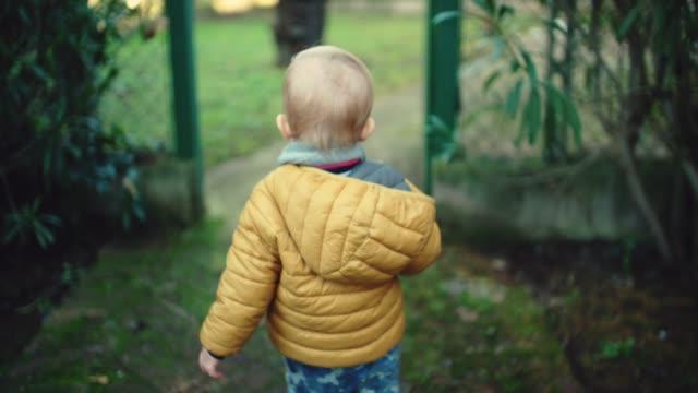 slow motion shot of toddler boy walking at park - abbigliamento da neonato video stock e b–roll