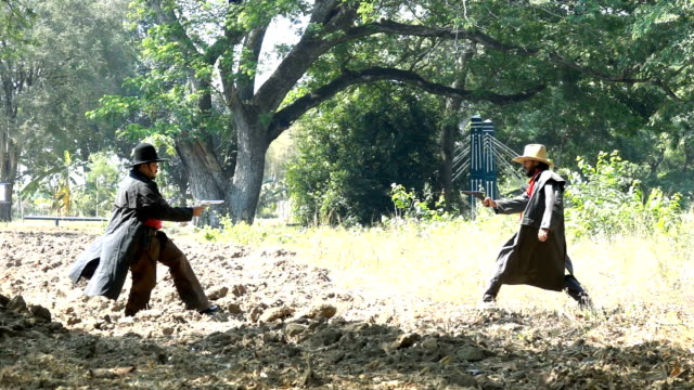 Slow Motion Shot Of Two Cowboys Fight By Shooting At Each Other