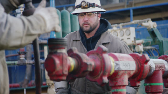 stockvideo's en b-roll-footage met slow motion shot van twee mannelijke oilfield werknemers pompen langs lijnen op een olie-en gasboorpad site op een koude, winterochtend - gas