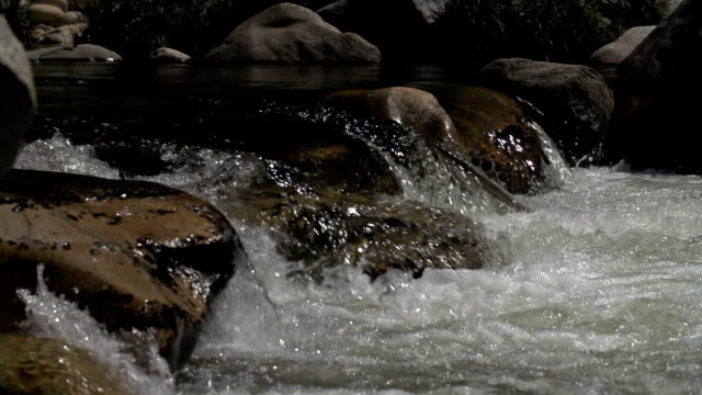 Slow motion shot of water flowing over rocks in river video
