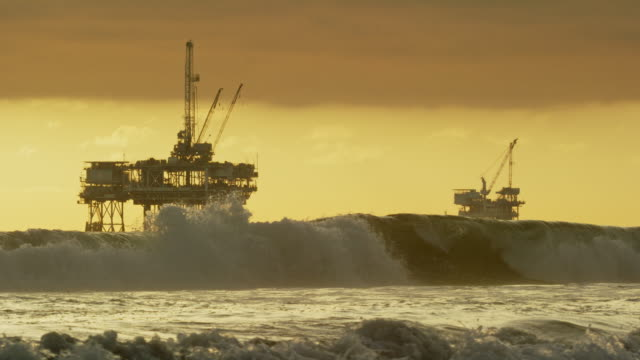 Slow Motion Shot of Waves Crashing onto the Shores of Huntington Beach in Southern California with Several Offshore Oil Drilling Rig Platforms and an Oil (Petroleum) Tanker on the Horizon in the Distance at Sunset under a Dramatic, Stormy Sky