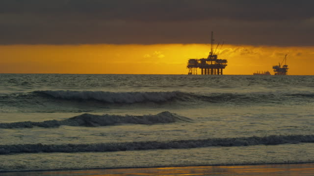 Slow Motion Shot of Waves Crashing onto the Shores of Huntington Beach in Southern California with Several Silhouettes of Offshore Oil Drilling Rig Platforms and an Oil (Petroleum) Tanker on the Horizon in the Distance at Sunset under a Dramatic, Stormy S