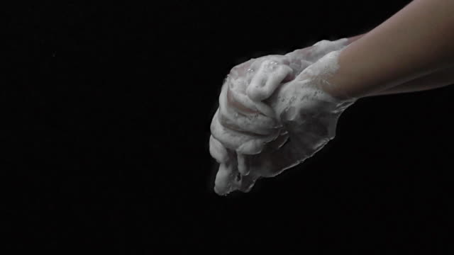 Slow motion shot of woman wash your hands on black background.