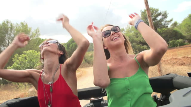Slow Motion Shot Of Women Dancing In Back Of Open Top Car