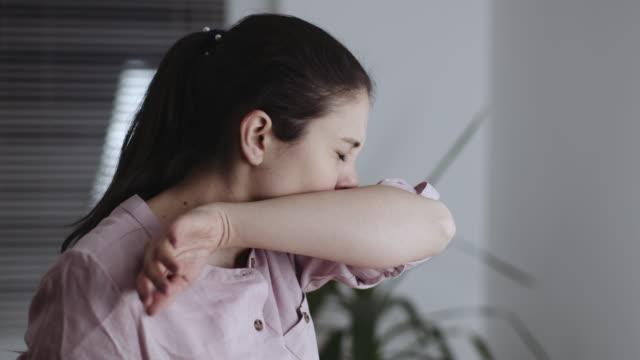 colpo al rallentatore di donne che starnutiranno nel gomito a casa. video stock - fragilità video stock e b–roll