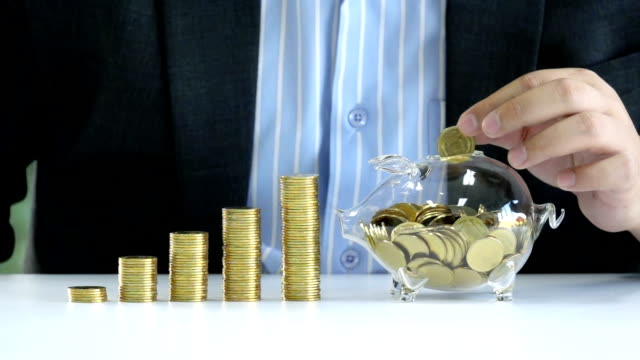 Slow Motion Shot Of Young Businessman drop golden coin into piggy bank glass for saving money to investment in the future