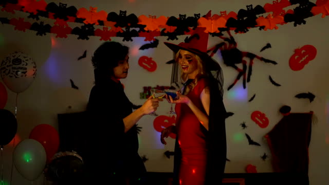 Slow Motion Shot Of Young Man And Woman Wearing Halloween Costumes Drinking Alcohol In The Party