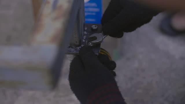 lang-bewegungs-schuss von young man mit wreng zum schrauben - steckschlüssel stock-videos und b-roll-filmmaterial