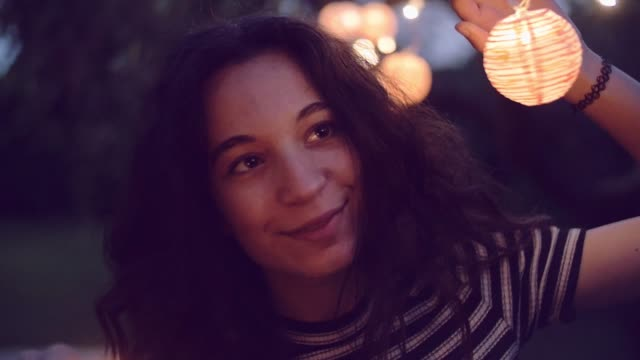 slow motion shot of young woman lighting sparklers in garden - lanterna attrezzatura per illuminazione video stock e b–roll