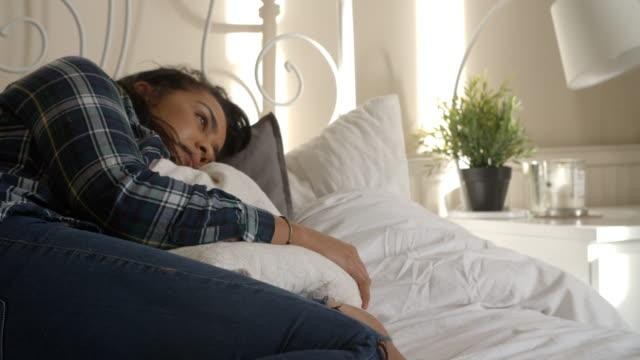 vidéos et rushes de le mouvement lent coup de jeune femme allongé sur le lit étreindre oreiller - femme seule s'enlacer