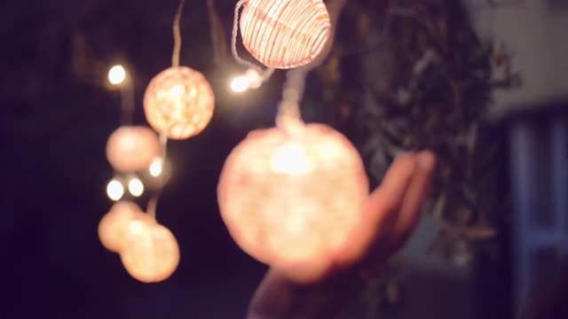 slow motion shot of young woman playing with lantern in the garden - lanterna attrezzatura per illuminazione video stock e b–roll