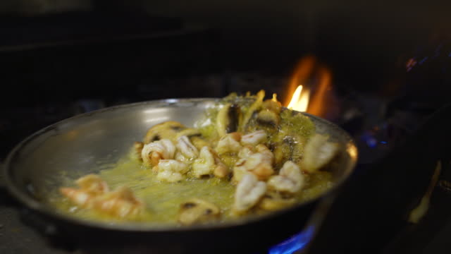 slow motion shrimp and mushroom flambe in pan of oil in commercial kitchen - tradycja filmów i materiałów b-roll