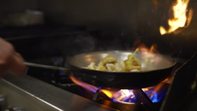 slow motion shrimp and mushroom flambe in pan of oil in commercial kitchen - struttura pubblica video stock e b–roll