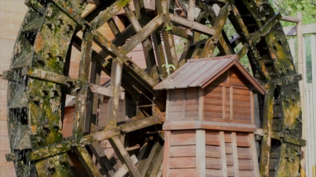 slow motion side view of an old river water wheel spinning in the sun - rivoluzione industriale video stock e b–roll