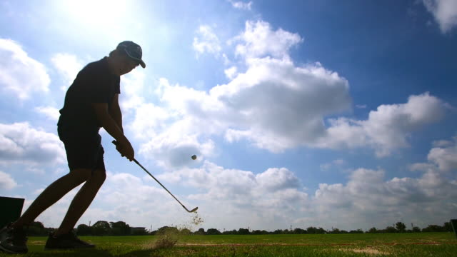 slow motion: silhouette asian young man hitting golf ball at golf course player exercise for good health