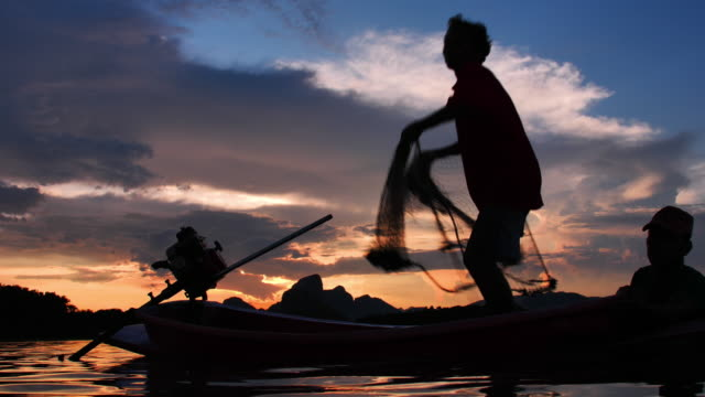 Slow Motion Silhouette of fishermen throwing fishing net during sunset with boats at the lake. Concept Fisherman's life style. Lopburi, Thailand.