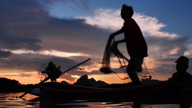 slow motion silhouette von fischern, die bei sonnenuntergang mit booten am see fischernetz werfen. konzept fisherman lebensstil. lopburi, thailand. - netzgewebe stock-videos und b-roll-filmmaterial
