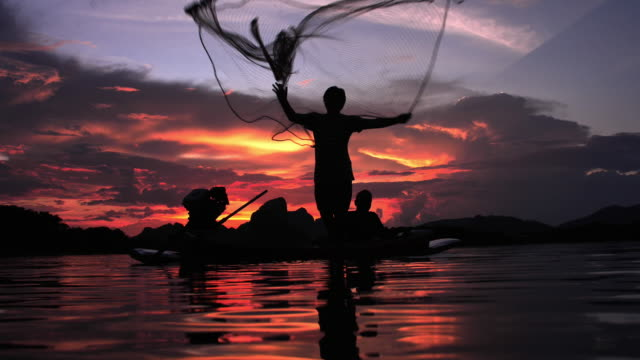 湖でボートで日没時に漁網を投げる漁師のスローモーションシルエット。コンセプトフィッシャーマンのライフスタイル。ロッブリー、タイ。 - 漁師 外人点の映像素材/bロール