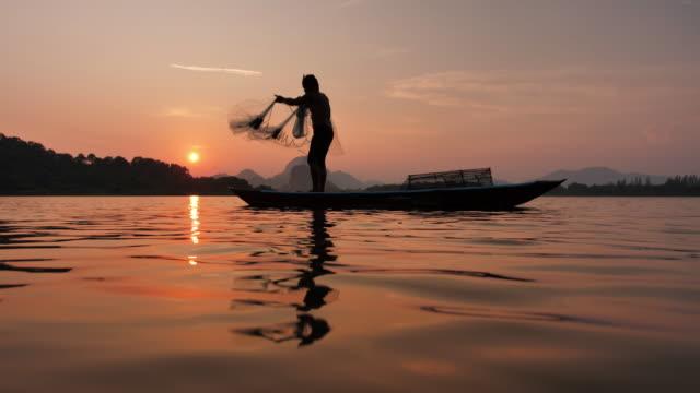 湖でボートで日没時に漁網を投げる漁師のスローモーションシルエット。コンセプトフィッシャーマンのライフスタイル。ロッブリー、アジア、タイ。 - 漁師 外人点の映像素材/bロール