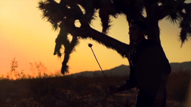 slow-motion-silhouette der mann bläst feuer in der wüste bei sonnenuntergang - stuntman stock-videos und b-roll-filmmaterial
