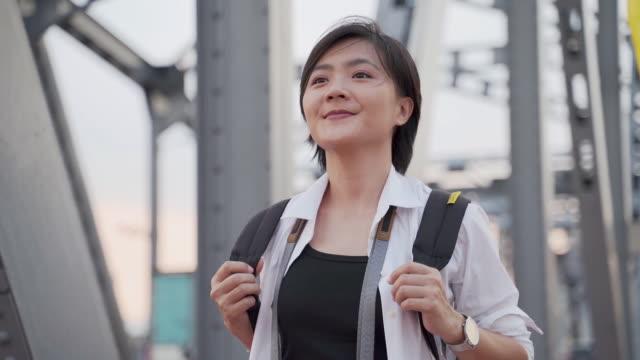 Slow motion: Smile Asian woman walking on the bridge video