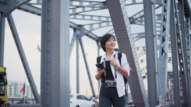 Slow motion: Smiling woman in white shirt use smartphone and walking on bridge video