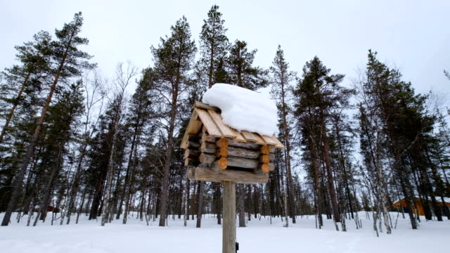 slow motion : snowy wooden mailbox on small town street. winter of lapland