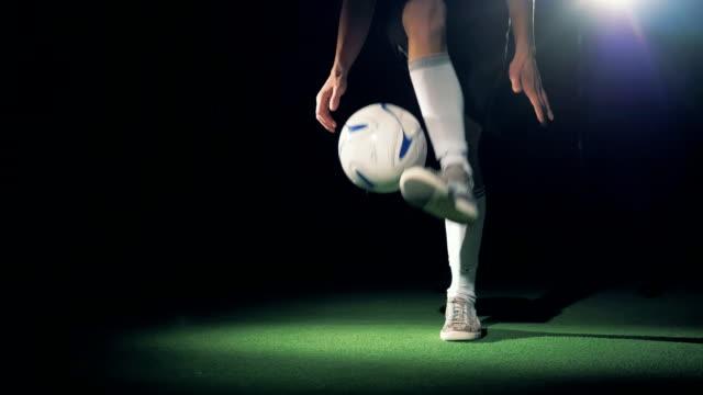 stockvideo's en b-roll-footage met slow motion voetballer spelen met een voetbal bal maken trucs. - sportcompetitie
