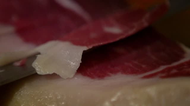 vídeos de stock e filmes b-roll de slow motion spanish people cutting iberian ham dish, traditional span food - presunto