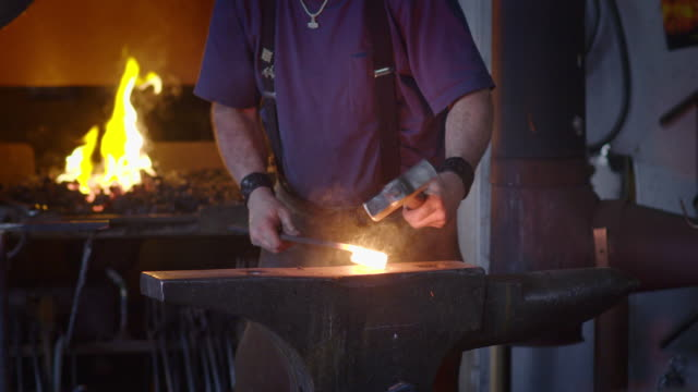 Slow motion spark shower as blacksmith hits hot metal on anvil Blacksmith creates a shower of sparks as he beats a piece of white hot metal with a hammer on an anvil.  Close up, originally recorded in 4K at 60fps. anvil stock videos & royalty-free footage