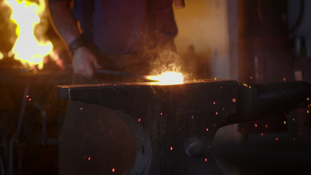 Slow motion sparks as blacksmith beats hot metal on anvil video