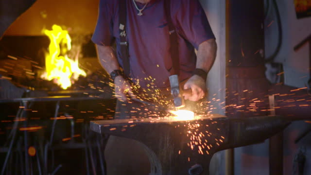 Slow motion sparks created by blacksmith hits hot metal on anvil video