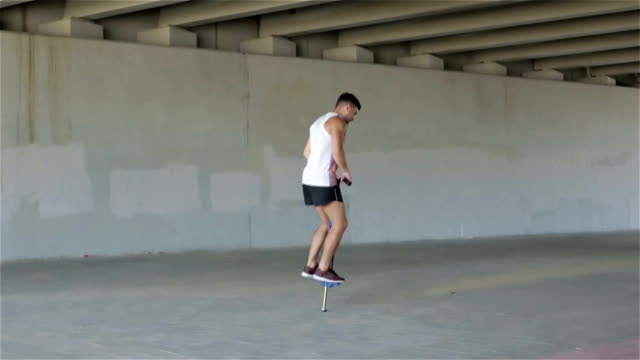 Slow motion. Sports guy in a white t-shirt and shorts jumping on the spring device under a bridge. video