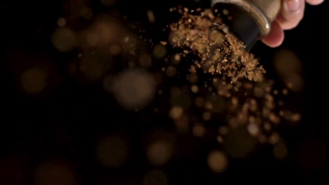 Slow motion: Sprinkling cayenne pepper on top of camera view.