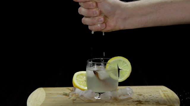 slow motion squeezing lemon juice into a glass. front view. - vodka video stock e b–roll