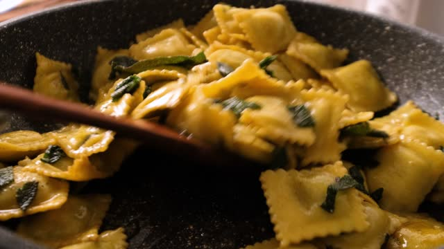 vídeos de stock e filmes b-roll de slow motion stiring and cooking dumpling pasta in frying pan with butter and sage - ravioli