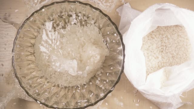 Slow motion strew white long grain rice in a bowl