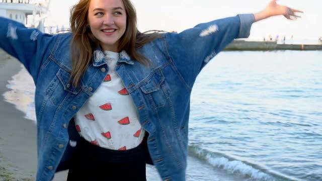 vídeos y material grabado en eventos de stock de pasos de mujer elegante de cámara lenta con confianza a lo largo de la orilla del mar y poses en cámara con sonrían en tarde de verano soleada - moda playera