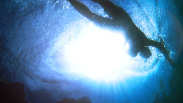 stockvideo's en b-roll-footage met slow motion swimming man silhouette with sun rays from bottom camera - ocean under water