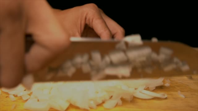 slow motion tattooed chef hands chopping onion on a wood cutting board