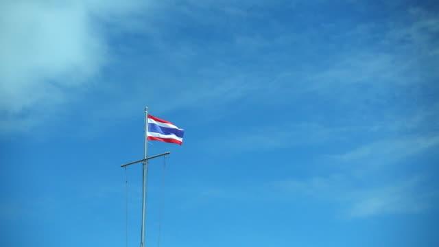 slow motion thai flag movement on blue sky - insygnia filmów i materiałów b-roll