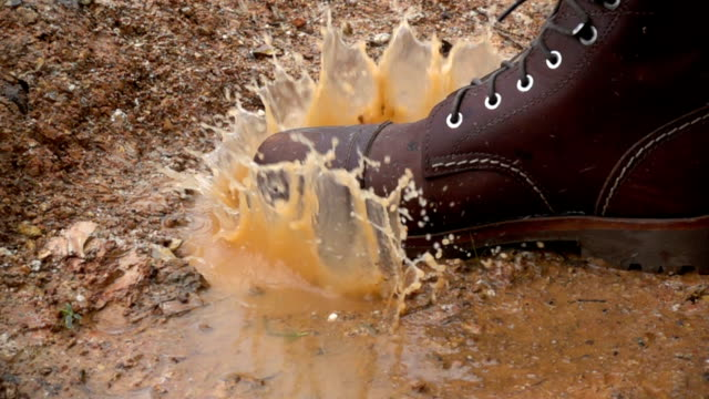 slow motion the boot stomping in a rain puddle making splash - fare un passo video stock e b–roll