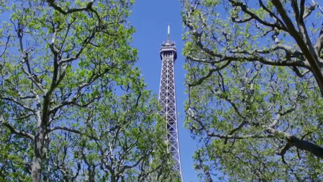 vídeos y material grabado en eventos de stock de cámara lenta de la torre eiffel, parís, a través de los árboles - stabilized shot